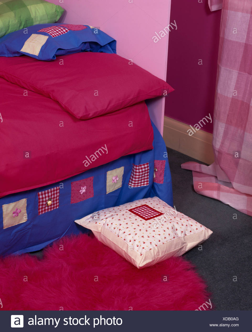 Bed with deep pink bedlinen and appliqued valance in nineties economy style bedroom - Stock Image