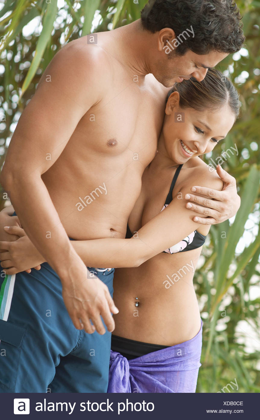 Affectionate young couple in swimwear near Beach - Stock Image