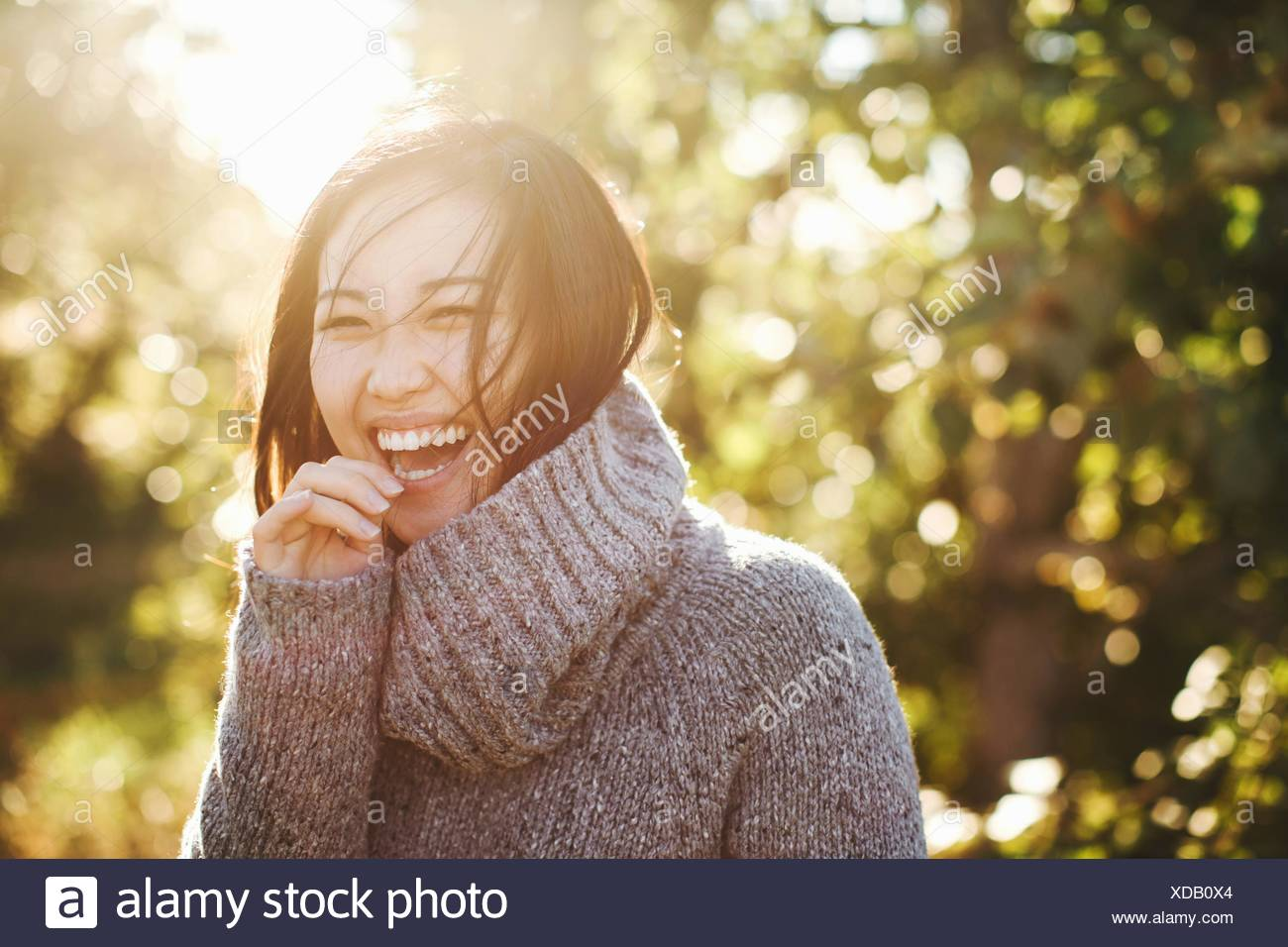 Portrait of young woman in rural environment, laughing - Stock Image