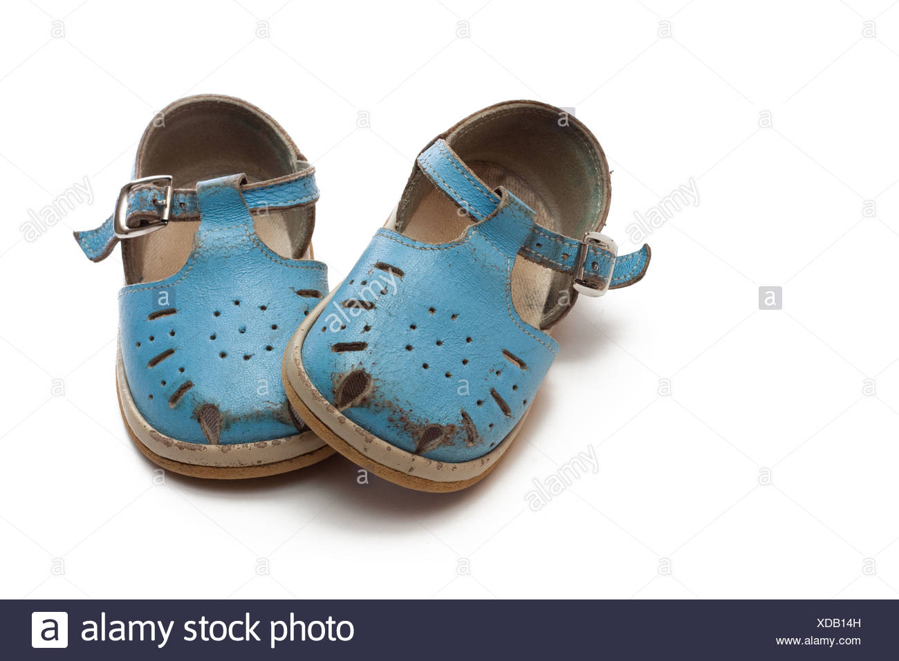 Worn-out childrens pair of shoes. The first boots. - Stock Image
