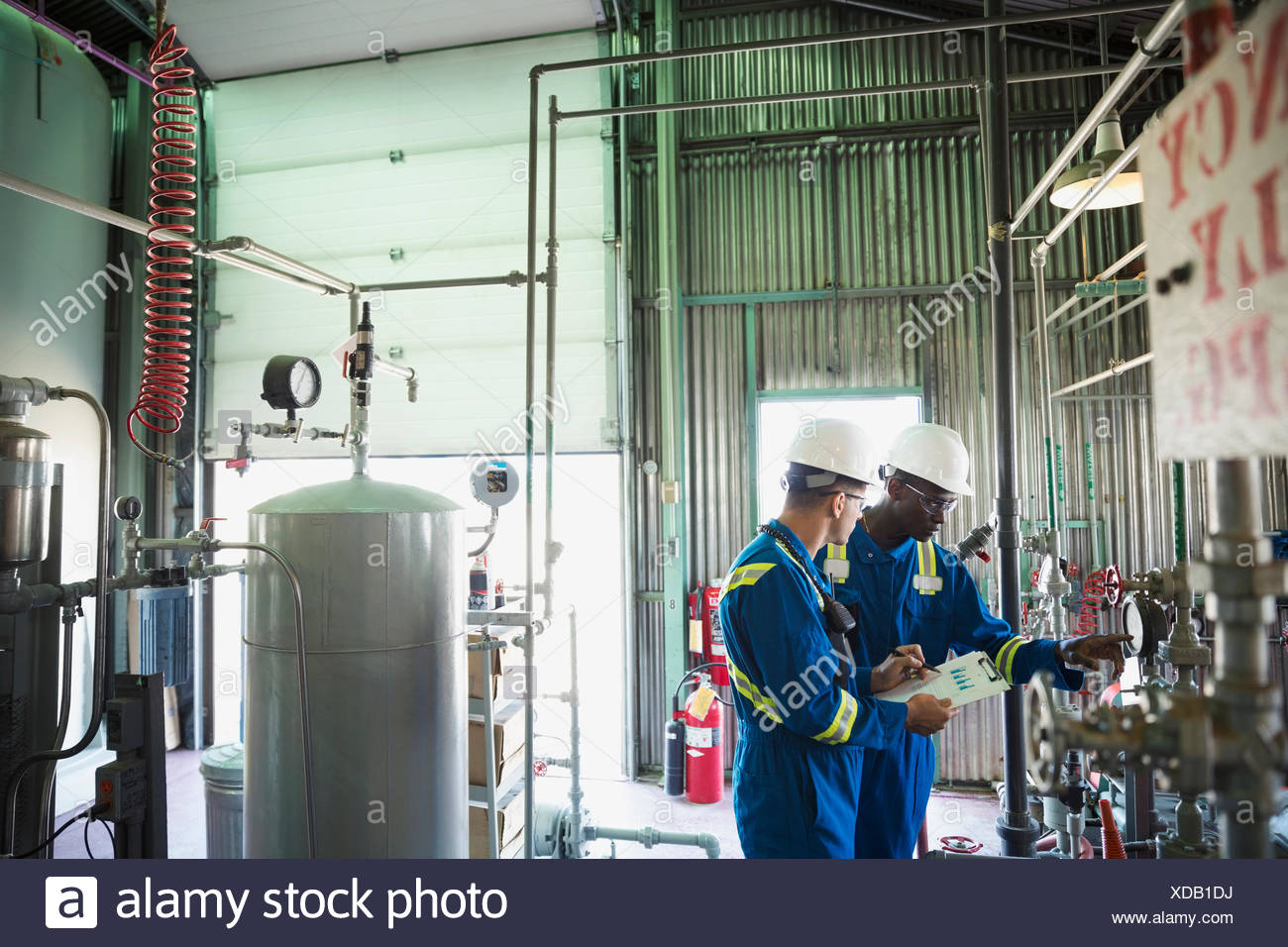 Male workers checking equipment gauge in gas plant - Stock Image
