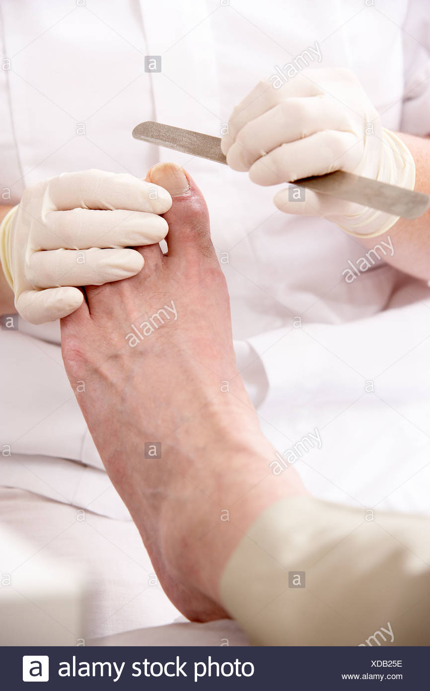 Chirpodist treating client in clinic - Stock Image