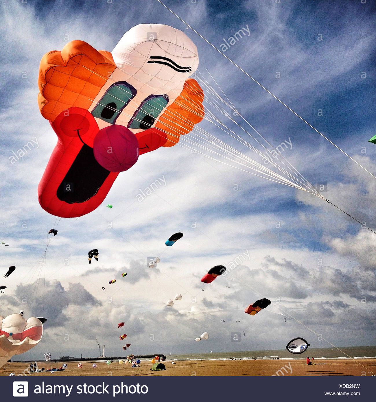 UK, Large Clown kite flying over beach - Stock Image