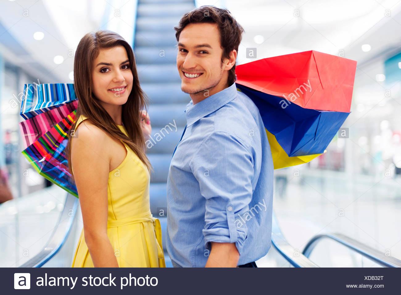 Smiling couple on escalator in shopping mall Debica, Poland - Stock Image