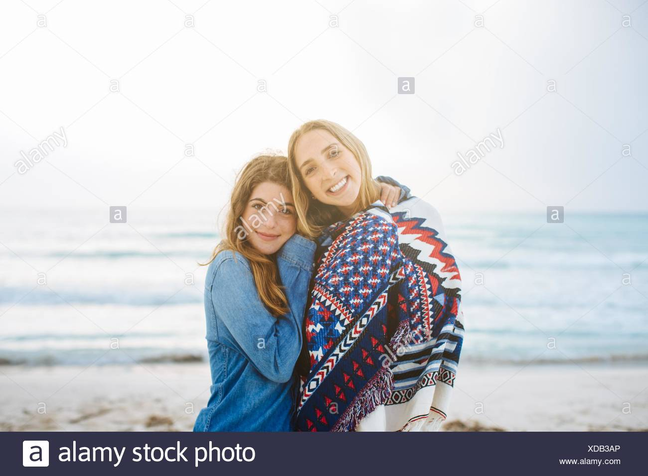 Portrait of two young female friends hugging on beach - Stock Image