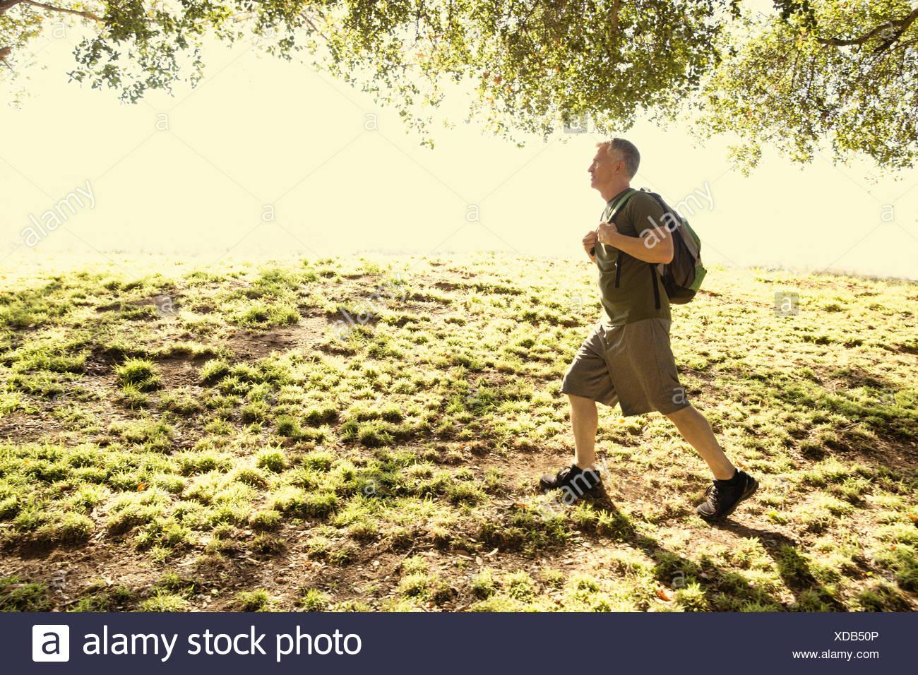 Mature man power walking in park - Stock Image