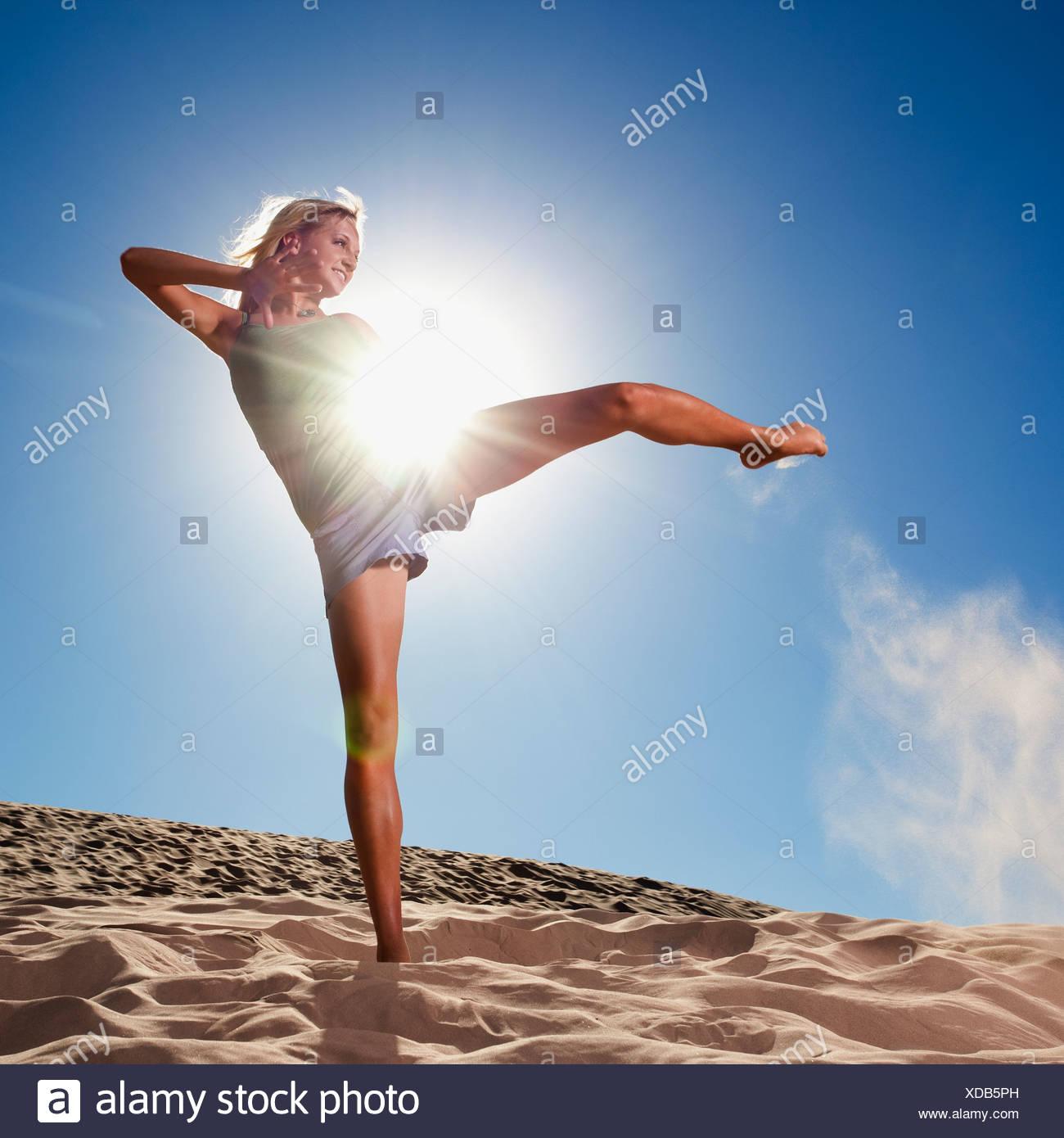 Female dancer kicking her leg on the beach - Stock Image