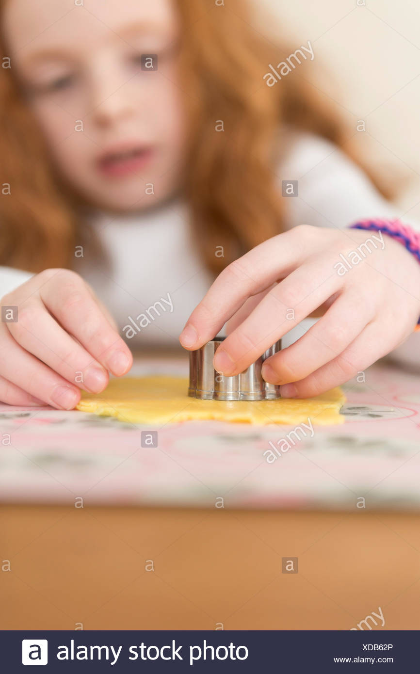Little girl making marzipan covered mine pies. Stock Photo