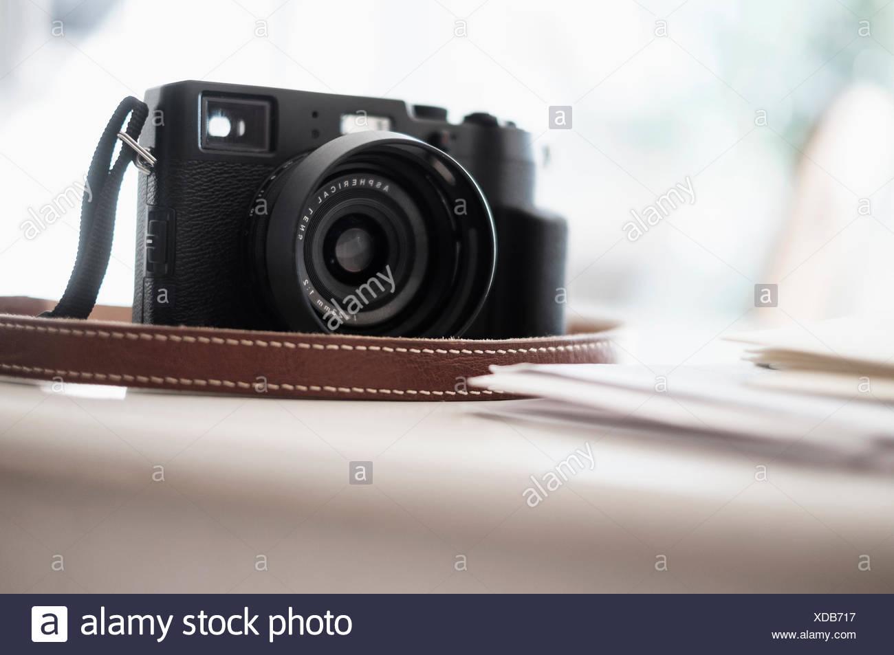 Digital camera on desk - Stock Image