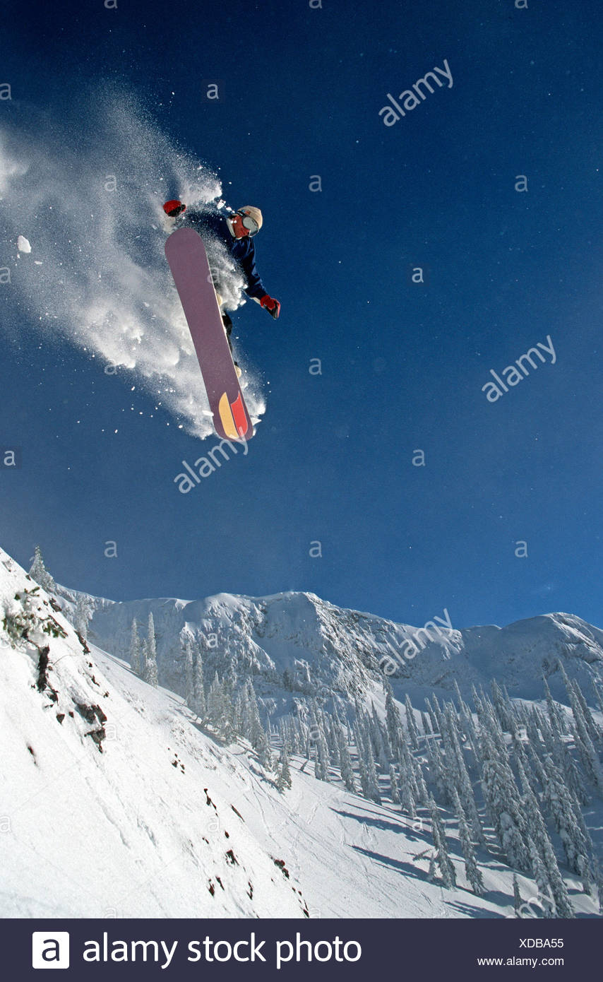 Young male adult jumping cliff on snowboard at Fernie Alpine Resort, BC, Canada. - Stock Image