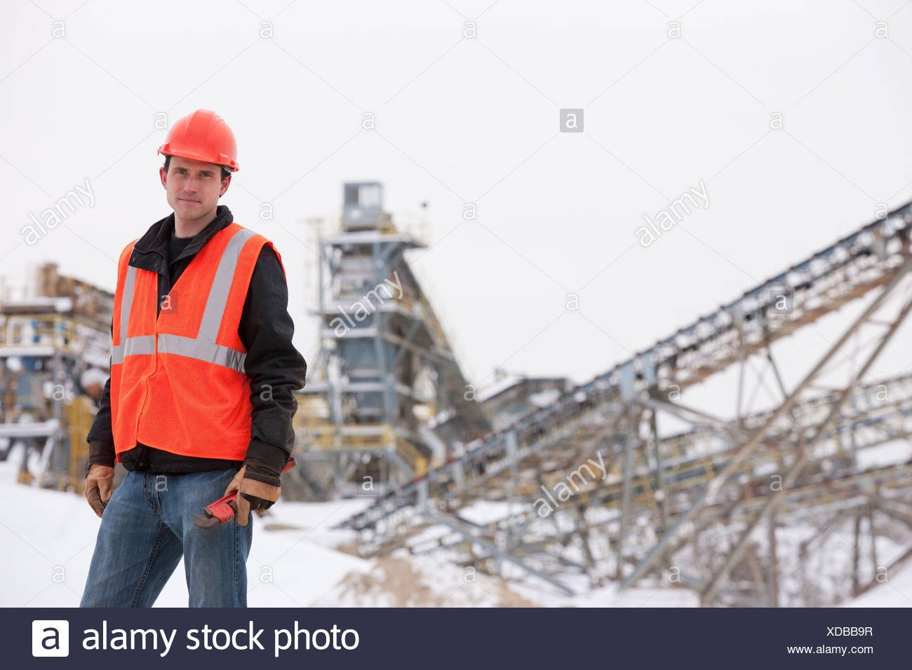 Engineer holding pipe wrench at a construction site - Stock Image
