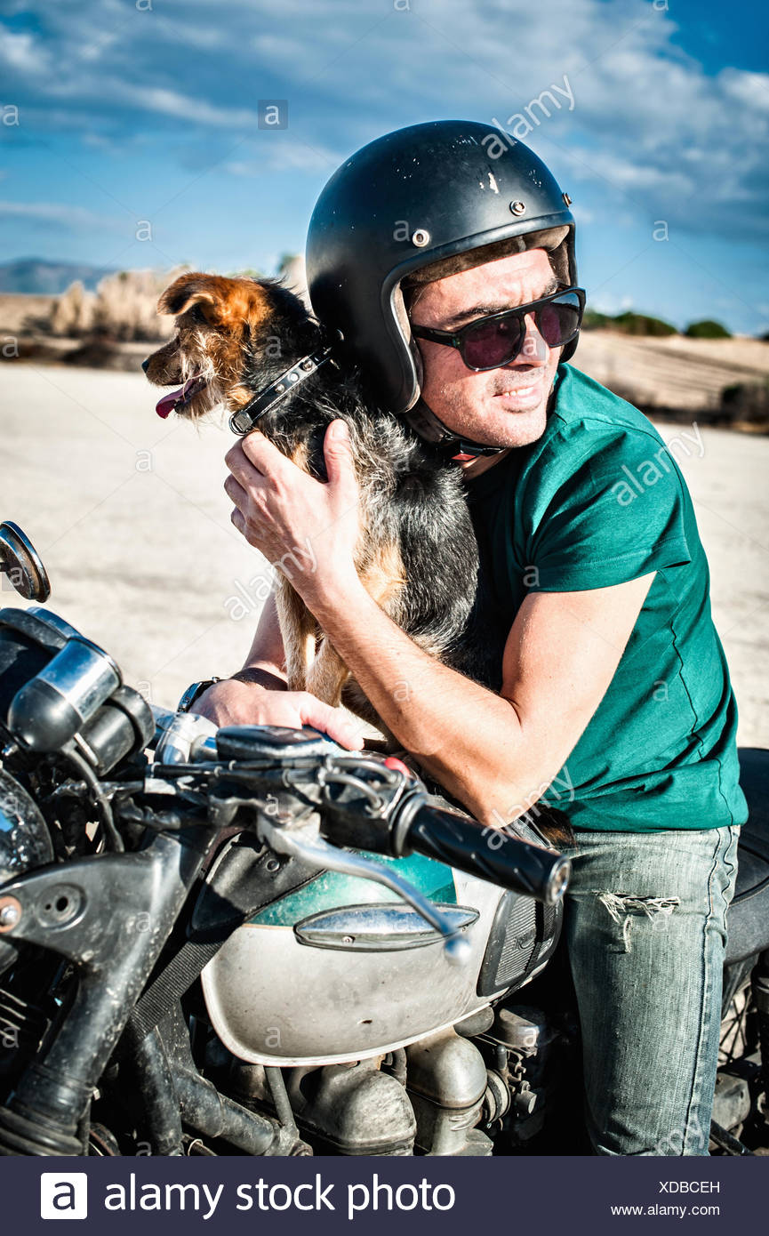 Mid adult man and dog sitting on motorcycle on arid plain, Cagliari, Sardinia, Italy - Stock Image