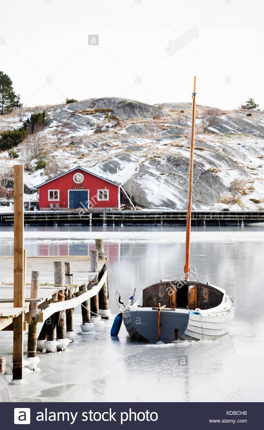 Sweden, Bohuslan, Orust, Mollosund, Boat by wooden jetty in winter Stock Photo