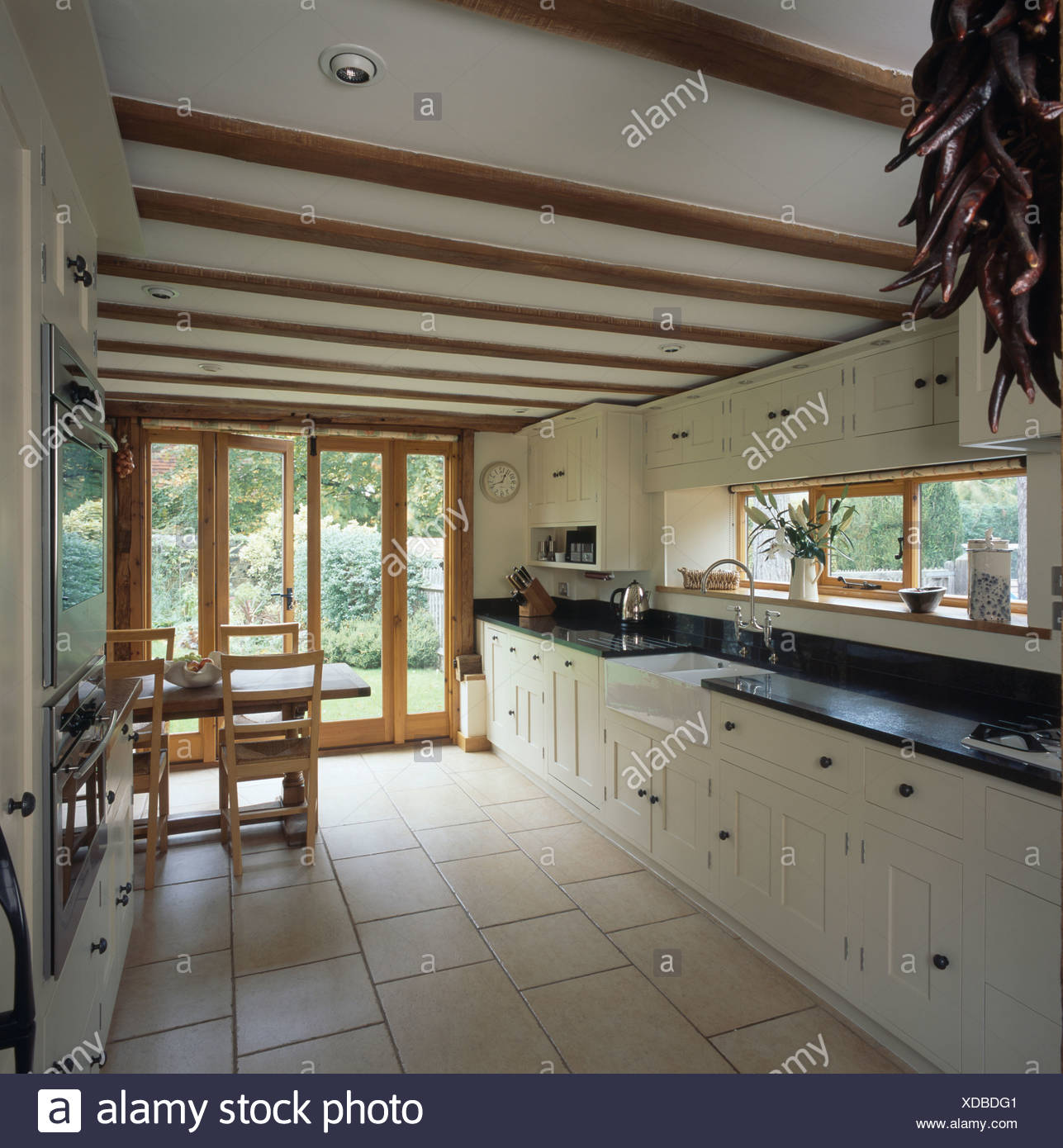 Cream ceramic floor tiles in country kitchen with white ...