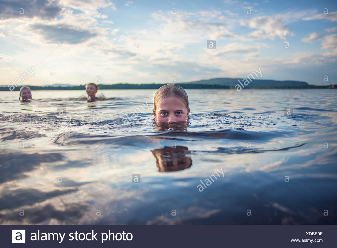 Father and children swimming in lake - Stock Image