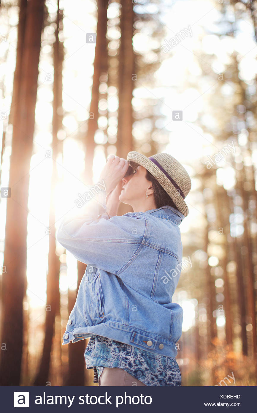 Mature female bird watching in forest - Stock Image