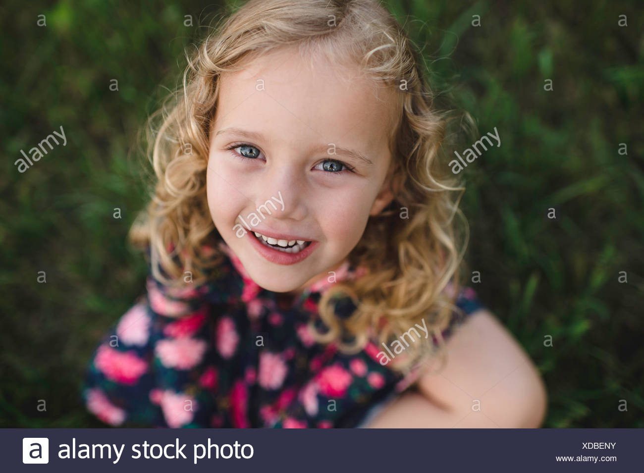 Overhead portrait of blond haired girl on grass - Stock Image