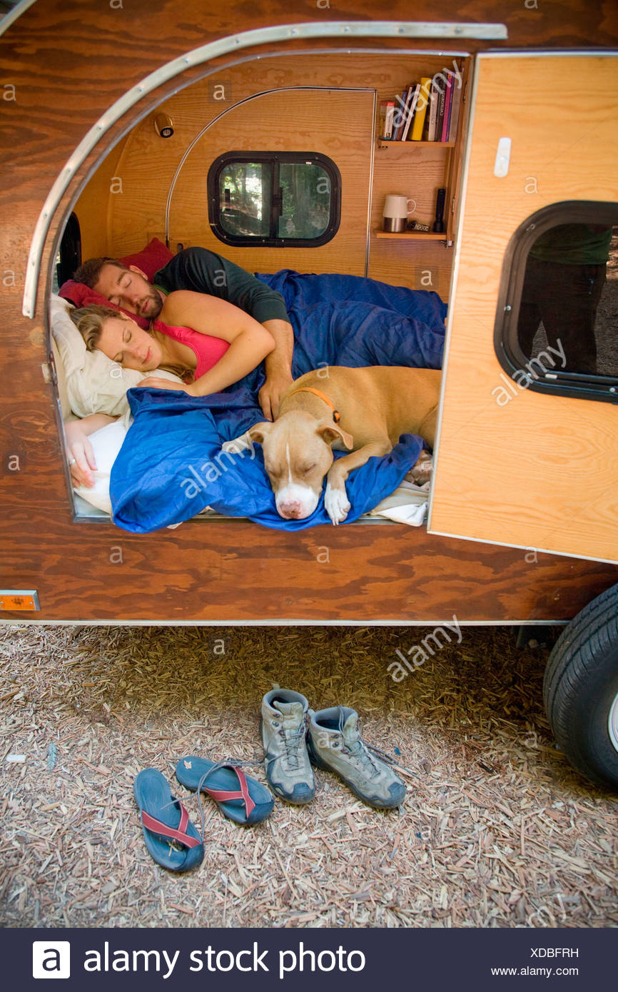 A young couple with their dog camping in a trailer near Big Sur. - Stock Image