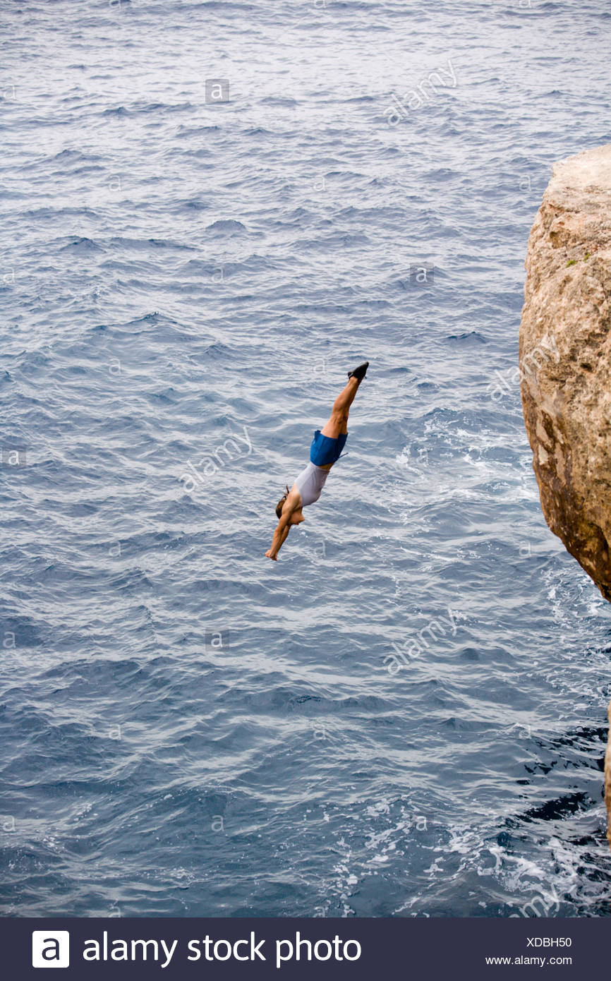 A woman diving over 10 meters off of a cliff and into the ocean. - Stock Image