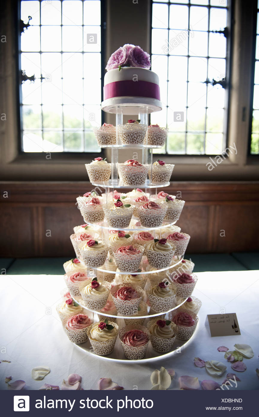 Frosted cupcakes on a seven tier cake stand a cupcake wedding cake England - Stock Image