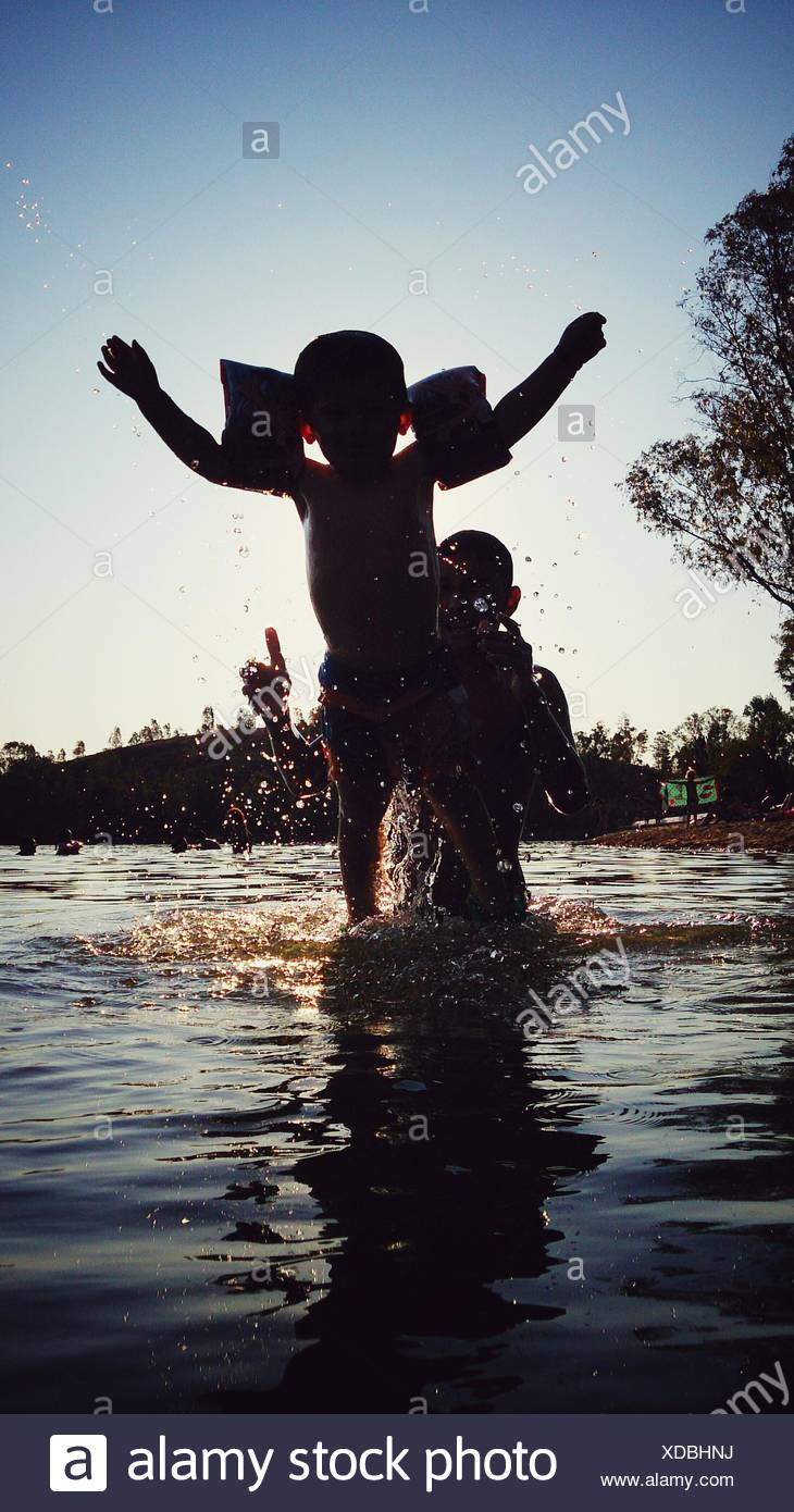 Father And Son Enjoying In River During Summer - Stock Image
