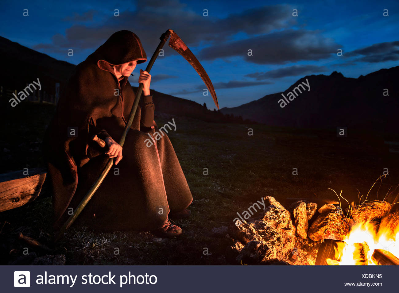 Person with scythe as personified death, grim reaper sitting at the fire, dark clouds - Stock Image