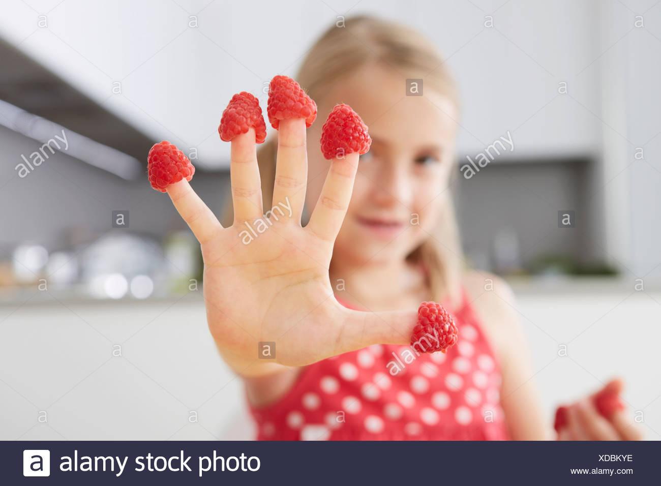 Girl putting raspberries on fingers Stock Photo