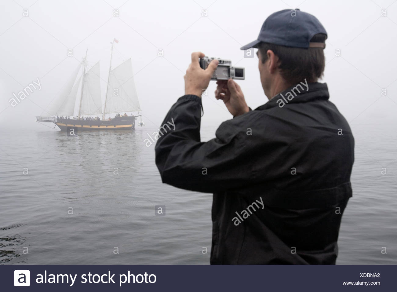 A man photographs sailing ship Liana's Ransom as it navigates thick fog in Halifax Harbour during the 2009 Tall Ships festival i - Stock Image