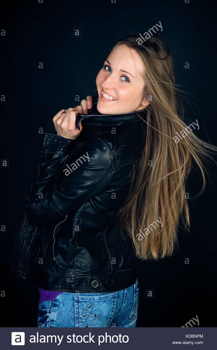 happy woman with long hair on black background - Stock Image