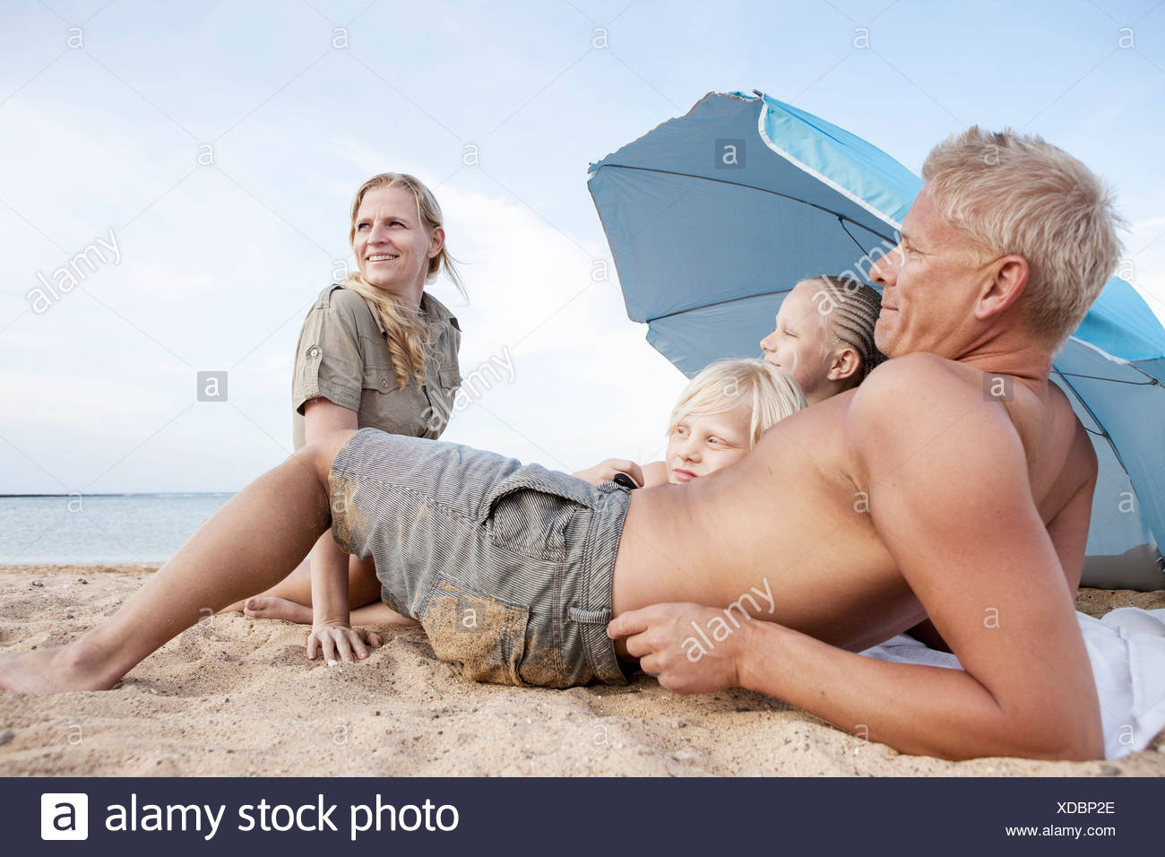Family with two children relaxing on beach - Stock Image