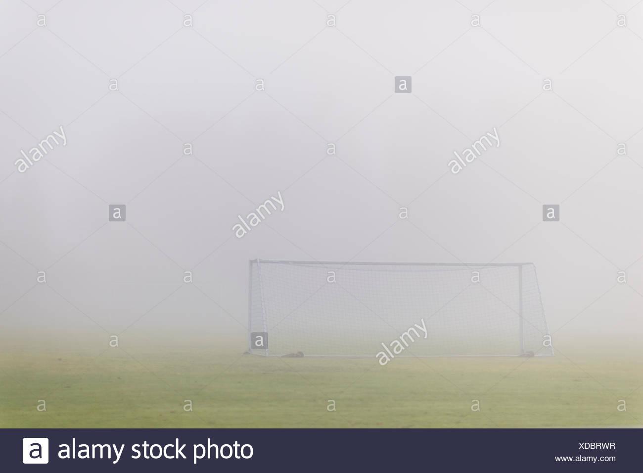 Sweden, Vastmanland, Soccer field covered in fog - Stock Image