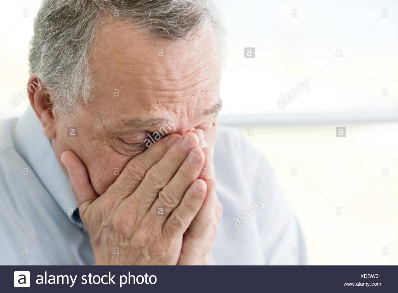 Senior man with hands covering face, close up. - Stock Image