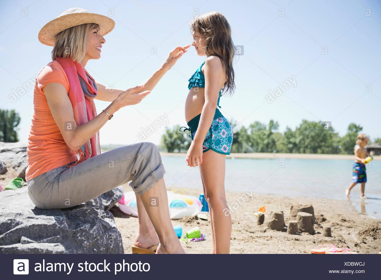 Grandmother applying sunscreen to granddaughter - Stock Image