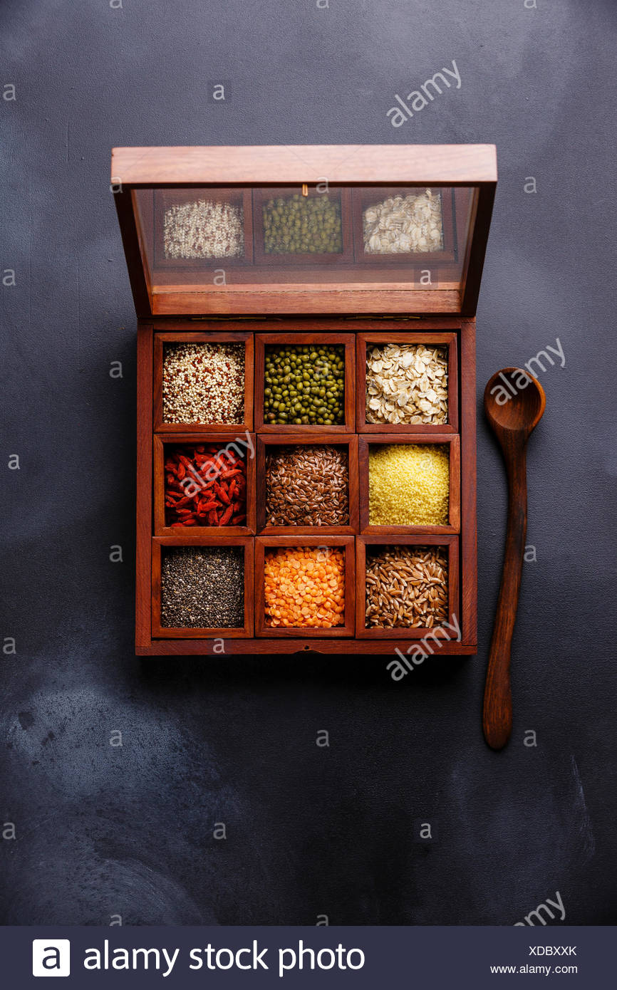 Superfoods and cereals selection in wooden box: oat, mung, quinoa, bulgur, flax seed, goji berry, polba, lentil and chia on dark background - Stock Image