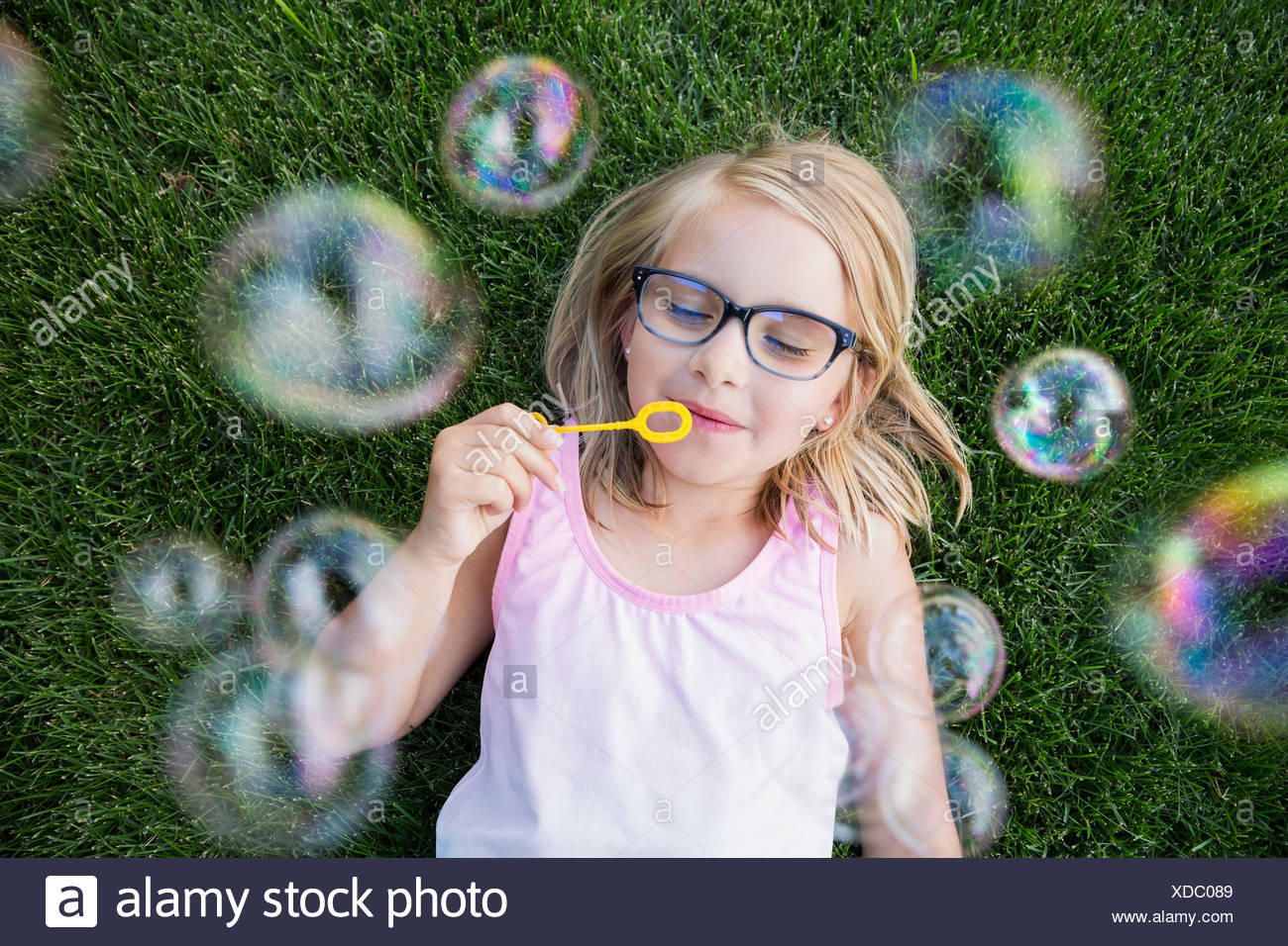 Overhead view blonde girl with eyeglasses blowing bubbles Stock Photo