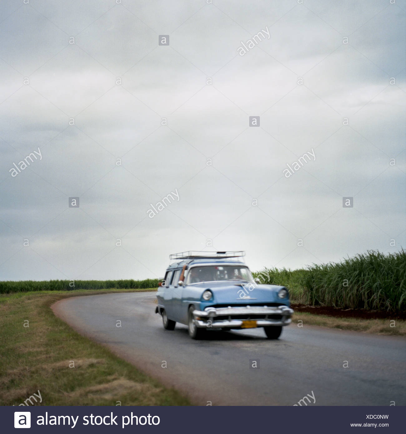 A classic station wagon drives a highway near Carlos Rojas, Cuba. - Stock Image