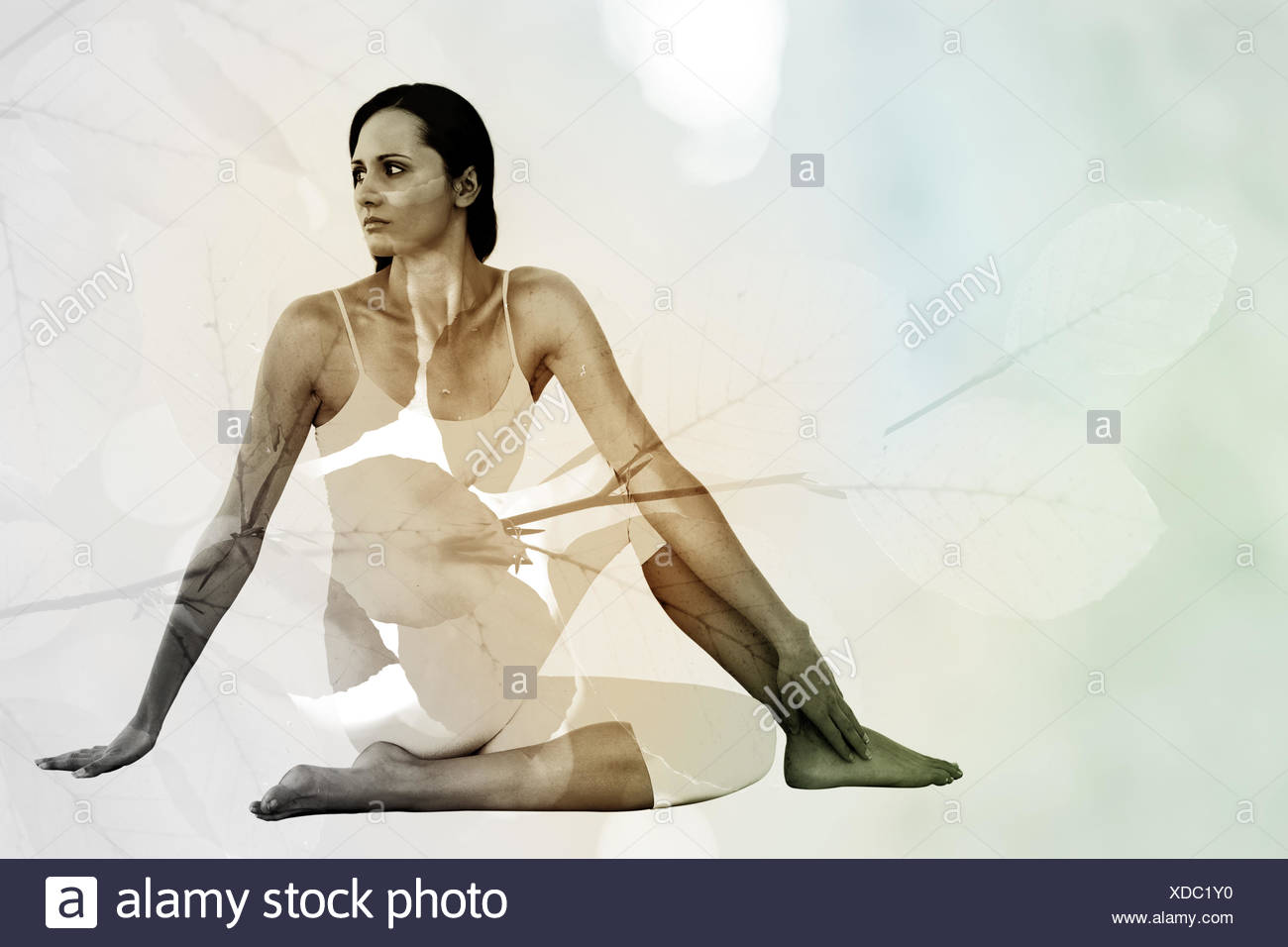 Composite image of fit woman doing the half spinal twist pose in fitness studio - Stock Image