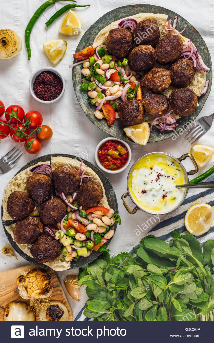 Turkish meatballs aka koftes served on pita bread on two copper plates with cold bean salad and red onions photographed from top view. Yogurt sauce, h Stock Photo