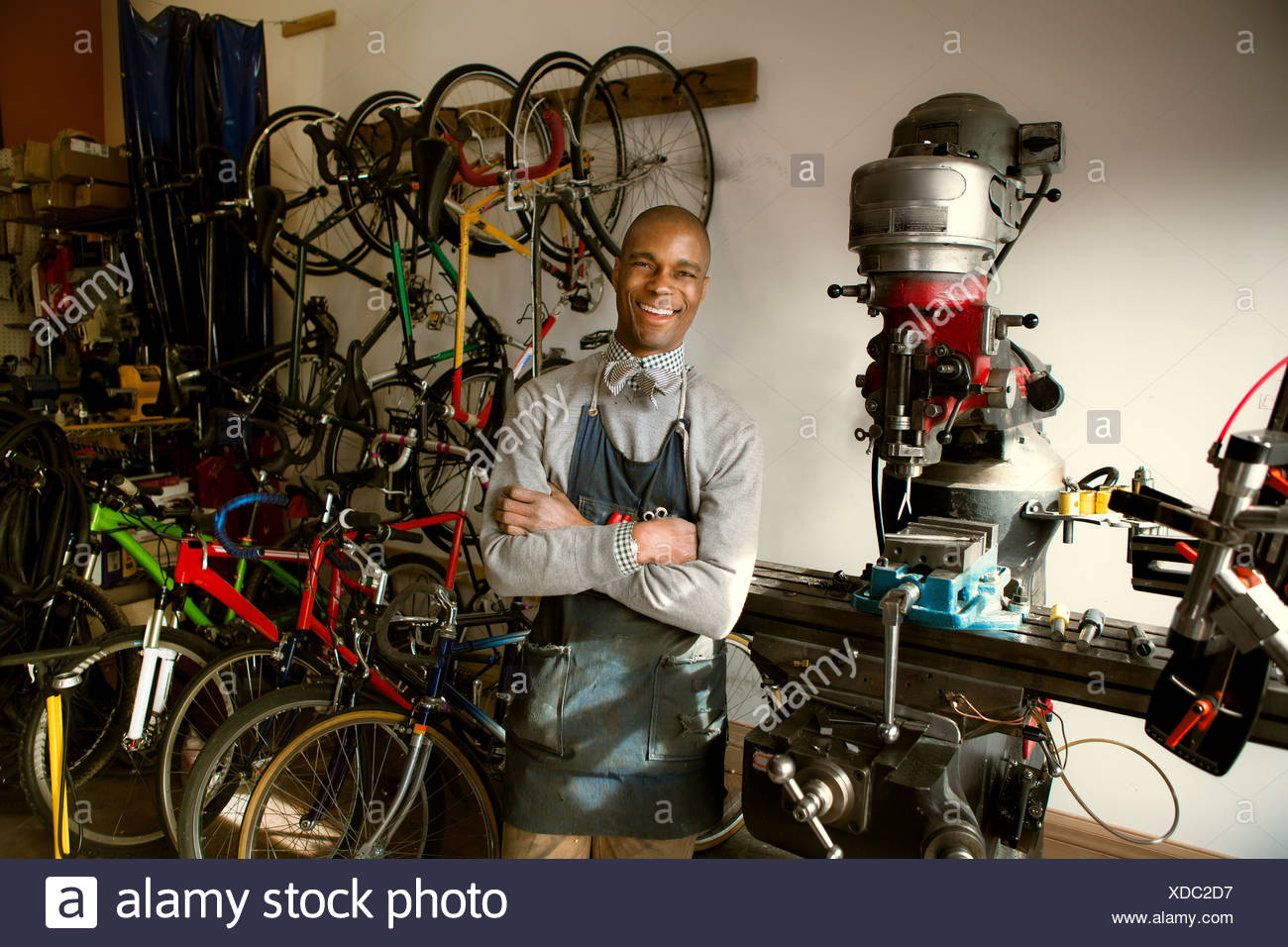Mechanic in bicycle workshop with arms crossed - Stock Image