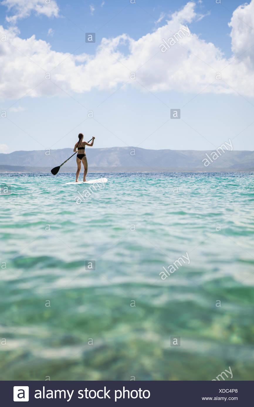 A woman paddle boarding in Croatia - Stock Image