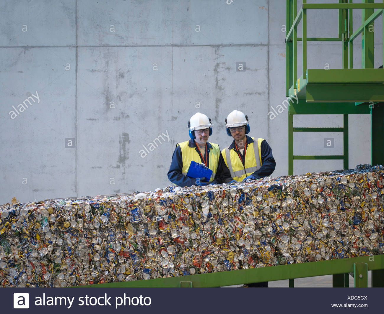 Workers Inspecting Bales Of Tin Cans - Stock Image