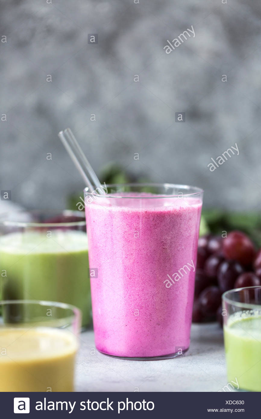 Several glasses of Multi-Colored Beet Smoothies are photographed from the front view. - Stock Image