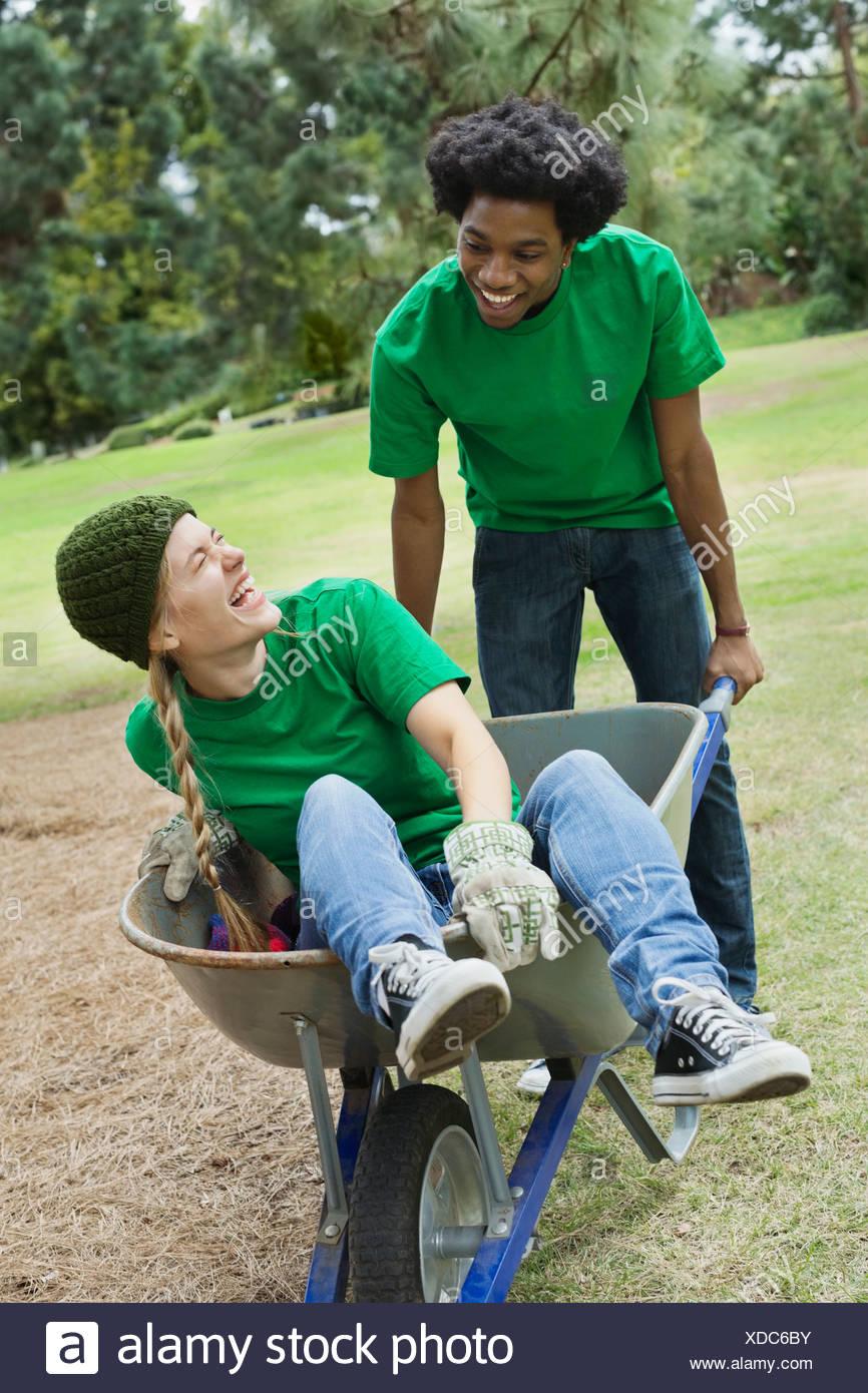 Young man pushing woman in wheelbarrow at park - Stock Image