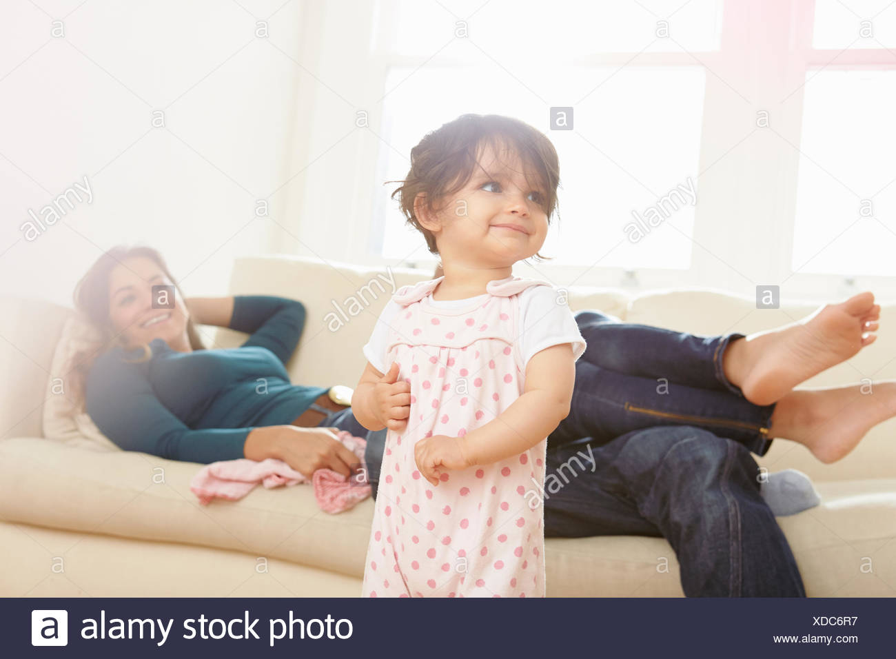 Baby girl toddling in living room with parents watching - Stock Image