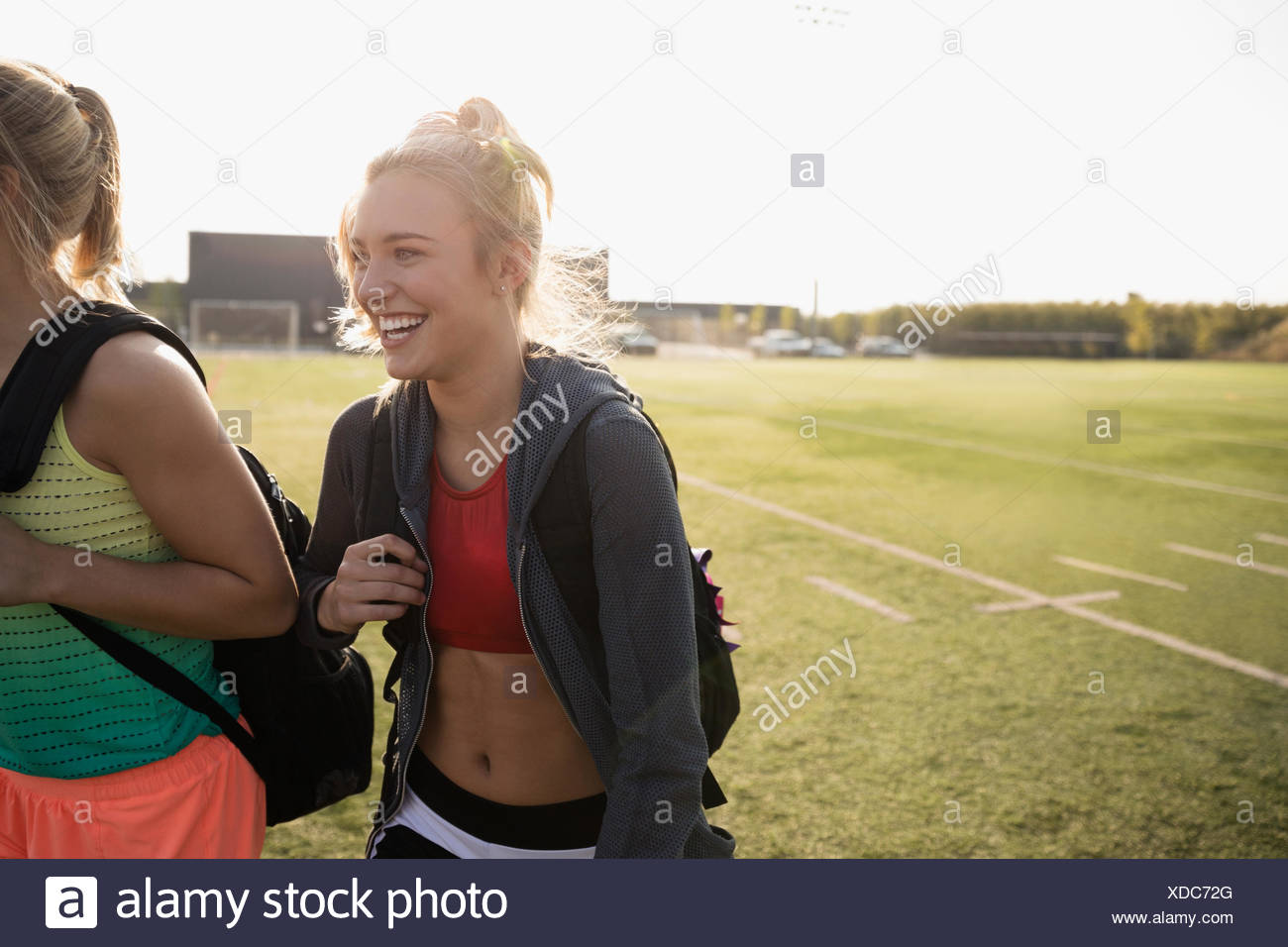 Smiling teenage girl high school cheerleader walking on sunny football field - Stock Image