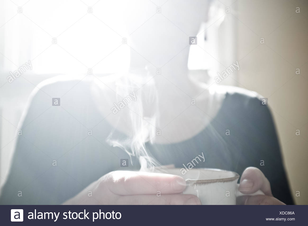 USA, Wyoming, View of woman drinking hot tea or coffee in cafe - Stock Image