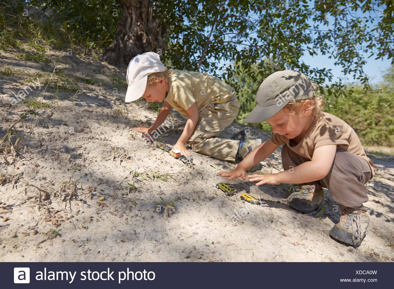 Two young boys, playing with toy cars on sand - Stock Image