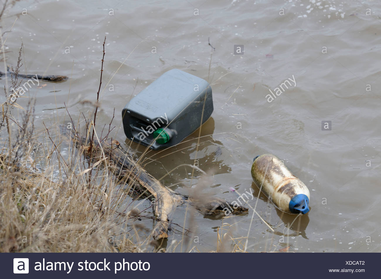 Flooded river with flotsam along the bank, environmental pollution - Stock Image