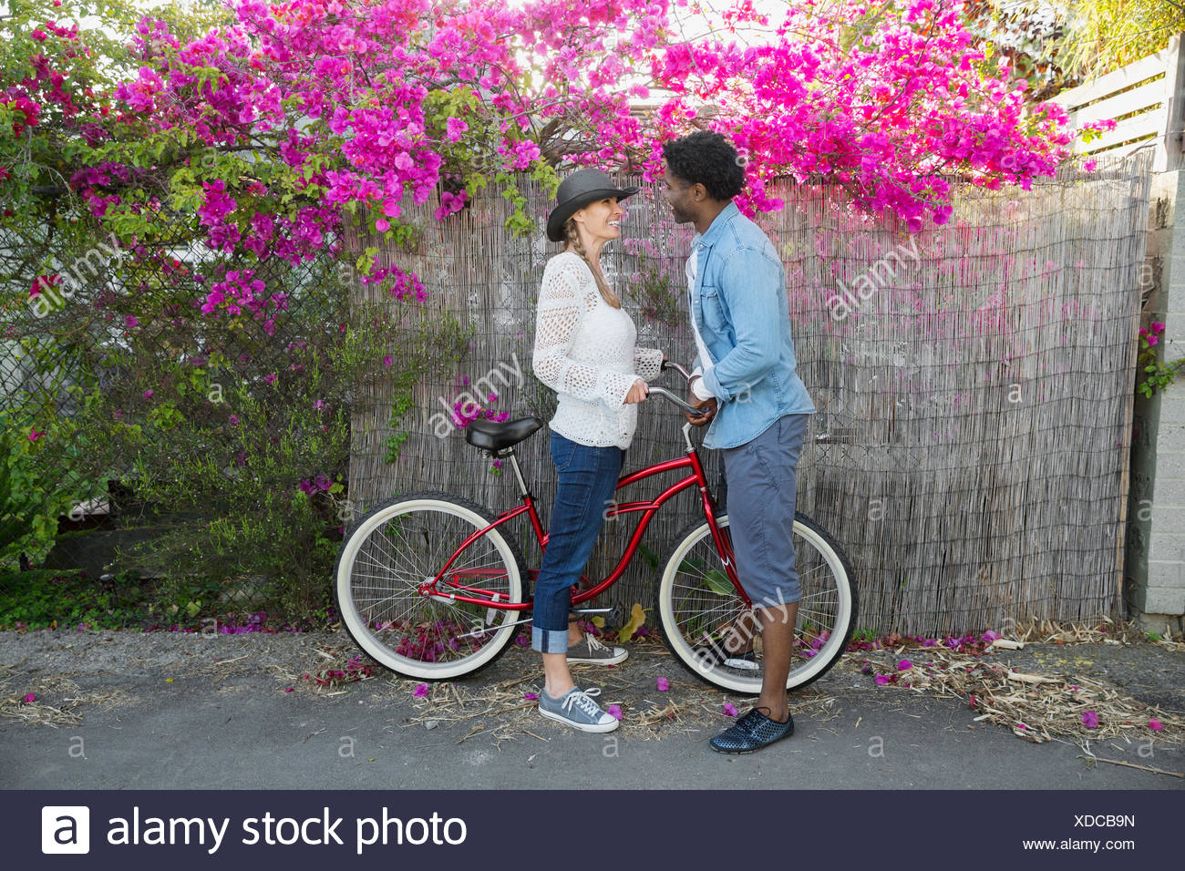 Affectionate couple with bicycle below bougainvillea tree - Stock Image