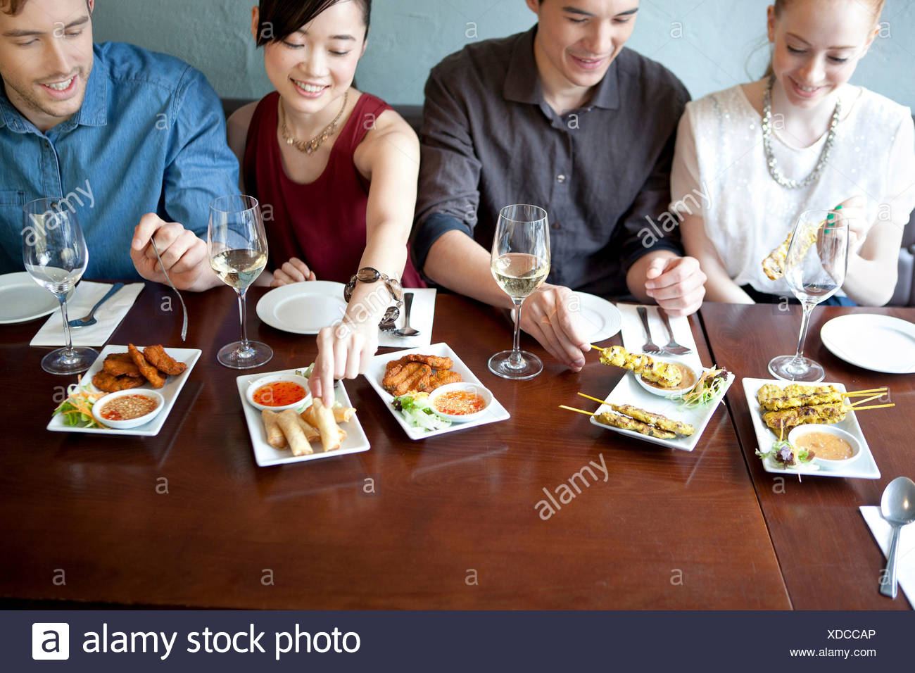Four friends eating food in restaurant - Stock Image
